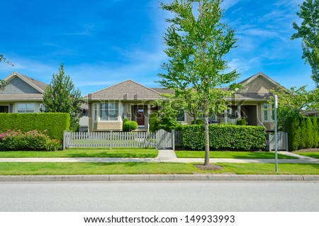 Nice looking house behind the green and wooden fence at the empty street in the suburbs of Vancouver, Canada. - stock photo