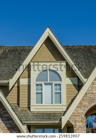 Nice looking window at the roof of the house. Vertical. - stock photo