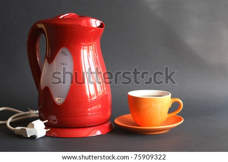 Nice modern red electric kettle near cup of tea on dark background - stock photo