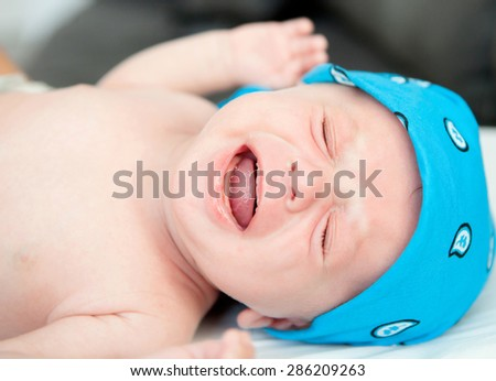 Nice newborn in diaper crying inconsolably - stock photo