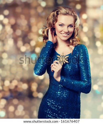 nice picture of an attractive young brunette girl with wavy hair well dressed with blue shining evening dress looking at the camera - stock photo