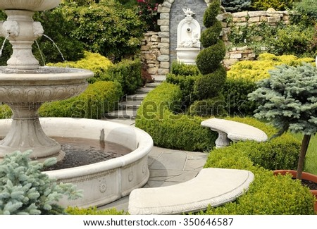 Nice place in the garden with a fountain. - stock photo