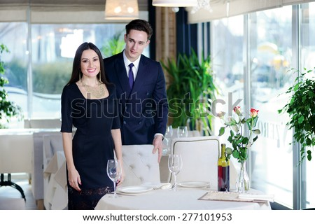 Nice romantic dinner at a restaurant. Young couple visits a restaurant. Woman standing near a man while the man sat down at the table and a woman looking directly into the camera - stock photo