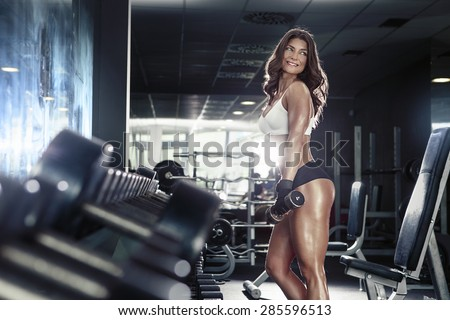 Nice sexy woman doing workout with dumbbells  in gym - stock photo