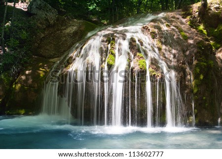 Nice small waterfall in deep forest - stock photo