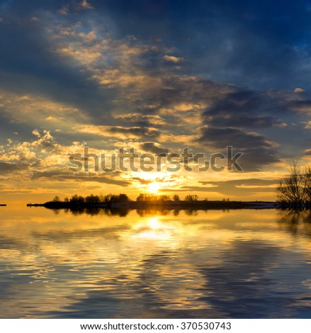Nice sunset over lake water surface - stock photo
