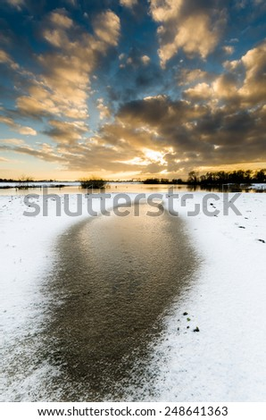 nice sunset with snow and water - stock photo