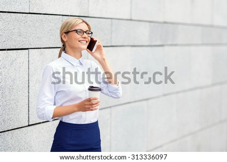 Nice talk. Cheerful attractive young business woman holding mobile phone and talking on it while standing near office building. - stock photo