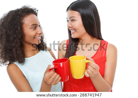 Nice tea party. Cheerful young ladies looking at each other and smiling while reveling in drinking tea - stock photo