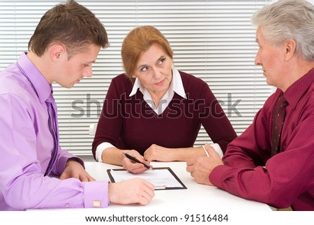 nice three business people sitting at office - stock photo