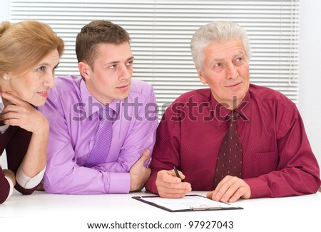 nice three business people sitting at table - stock photo