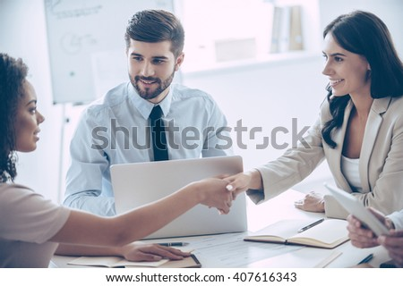 Nice to meet you! Two beautiful women shaking hands with smile while sitting at the office table with their coworker - stock photo