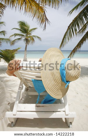 Nice vacation picture with woman sitting on a lounger - stock photo