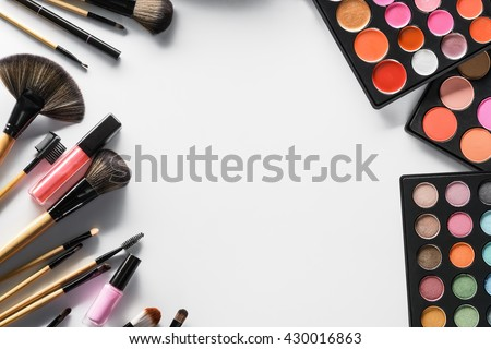 Nice wallpaper for girls and women with qualitative cocmetics and brushes for applying make-up. Collection of professional palettes with blushers, lipticks and eyeshadows of different colors. - stock photo