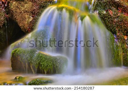 Nice waterfall on green stones - stock photo