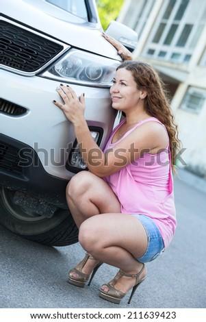 Nice woman sitting in high heels near own car bumper - stock photo