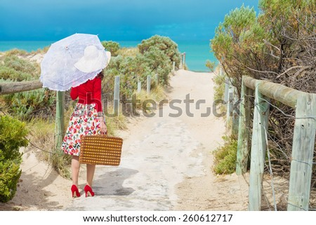 Nice Woman traveler in retro style dress walking through dunes to the beach. Local focus on the woman - stock photo