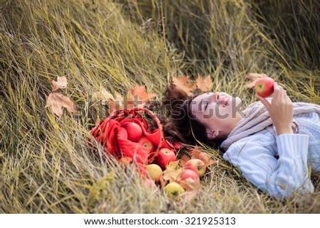 Nice woman with a basket full of red apples - stock photo