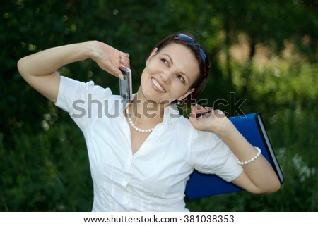 Nice woman with mobile phone on the nature in the morning - stock photo