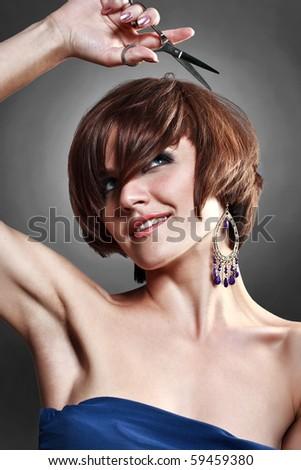 Nice  women  with scissors on  dark background - stock photo