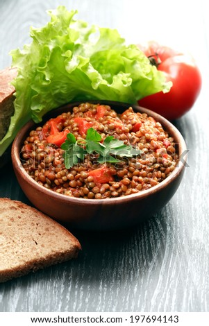 Nice wooden bowl full of hot lentil near bread and vegetables - stock photo