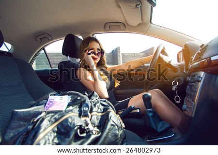Nice young adult blonde girl with blue eyes driving car with bag full of money. Inside car photo - stock photo