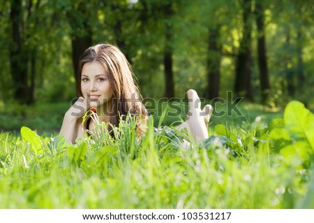 Nice young brunette girl lying down in the grass - stock photo