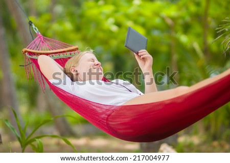 Nice young lady listen music and read book on e-ink reader in  hummock under palm trees on tropical beach - stock photo