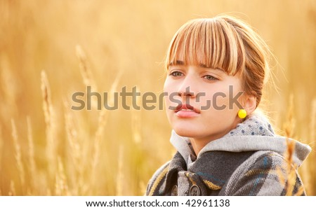 Nice young woman against yellow ripe field of wheat. - stock photo