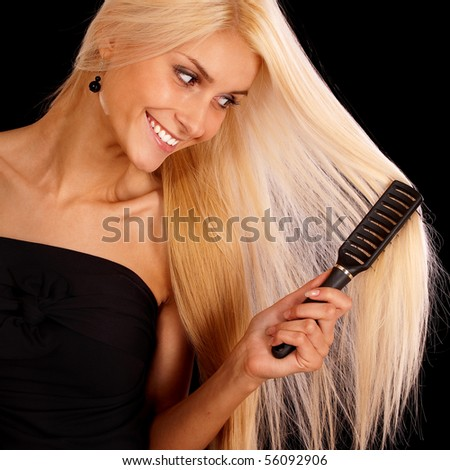 Nice young woman combs hair and smiles, it is isolated on black background. - stock photo