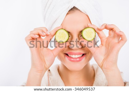 Nice young woman with cucumber, isolated on a white background - stock photo