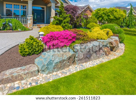 Nicely decorated colorful flowerbed with flowers, stones and bushes as a decorative elements. Landscape design. - stock photo