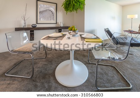Nicely decorated dining table in the luxury modern kitchen with the living room at the back. Interior design. - stock photo