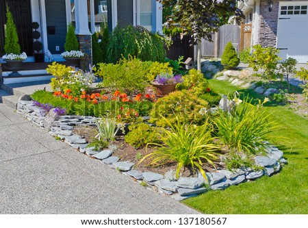 Nicely decorated flower bed, some flowers and nicely trimmed bushes on the front yard. Landscape design. - stock photo