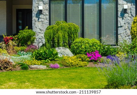Nicely decorated front yard. Flowers and stones in front of the house. Landscape design. - stock photo