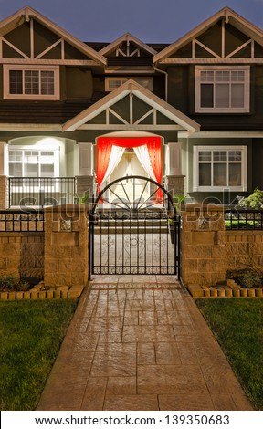 Nicely decorated house entrance with paved long doorway  at night, dawn time. - stock photo