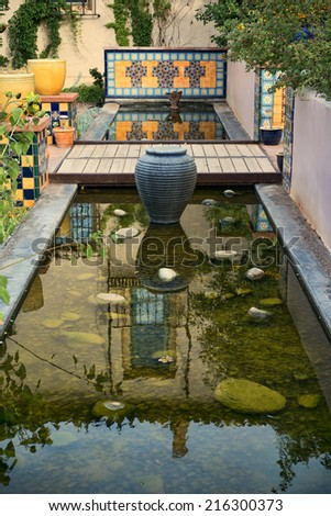 Nicely landscaped courtyard area, with pots, tile and reflecting pond - stock photo