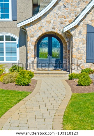 Nicely paved and designed doorway. Entrance to the house. - stock photo