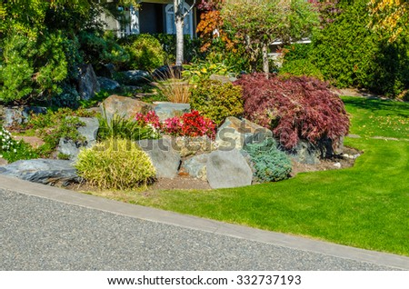 Nicely trimmed bushes, flowers and stones in front of the house, front yard. Landscape design. - stock photo