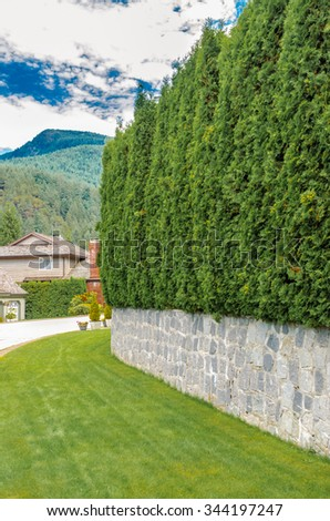 Nicely trimmed bushes, green fence, flowers and stones in front of the house, front yard. Landscape design. Vertical. - stock photo