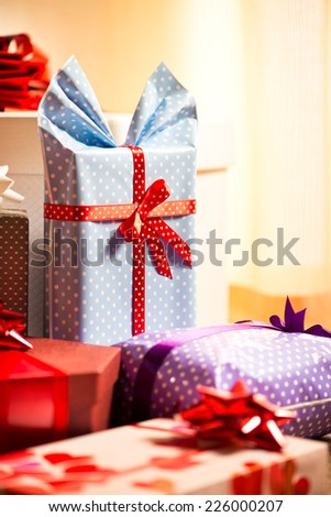 Nicely wrapped gifts with dotted wrapping paper and colorful ribbons. - stock photo