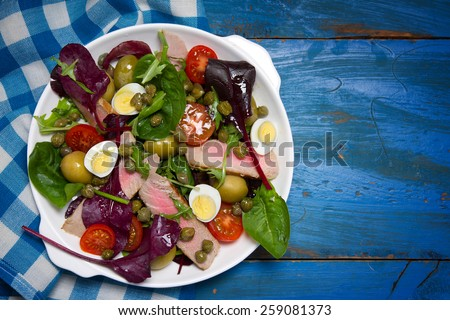 Nicoise salad with tuna, quail eggs, cherry tomatoes, olives and capers - stock photo