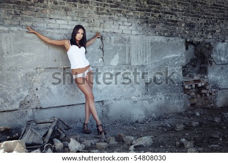 Nifty lady in the lingerie standing in old ruins - stock photo