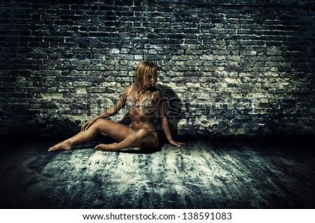 Nifty lady in underclothes with perfect figure by brick wall - stock photo