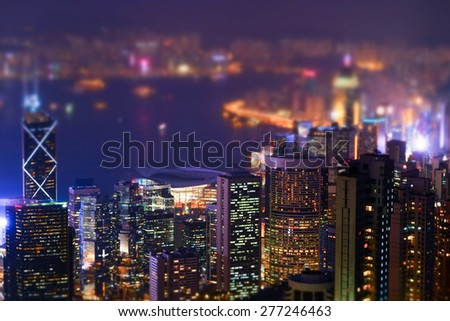 Night aerial view panorama of Hong Kong skyline and Victoria Harbor. Tilt shift effect. Abstract futuristic cityscape with modern skyscrapers  - stock photo