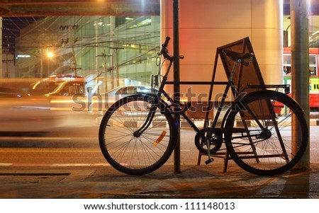 Night bicycle silhouette against city car light motion - stock photo