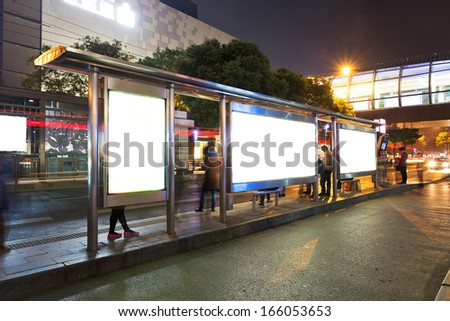 Night bus station with blank billboard - stock photo
