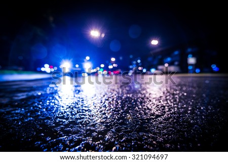 Night city after rain, approaching car headlights shine. View from a wide angle at the level of the asphalt, in blue tones - stock photo