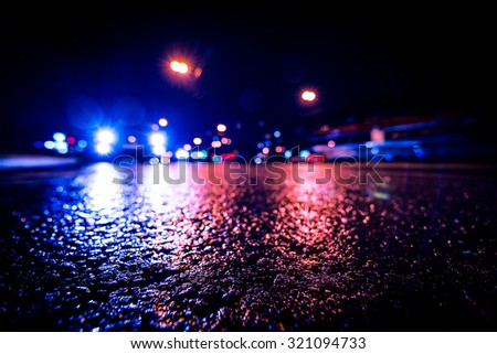 Night city after rain, approaching car headlights shine. View from a wide angle at the level of the asphalt, image vignetting and the blue toning - stock photo