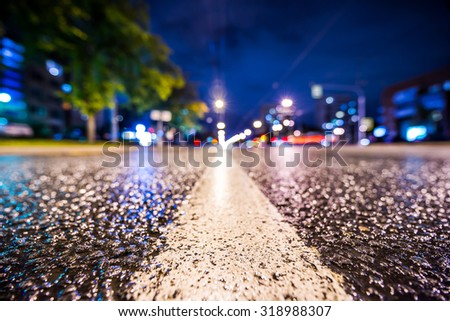 Night city after rain, the glowing lights of approaching cars. View from the level of the dividing line, in blue tones - stock photo